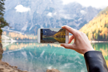 woman taking a photo of lake at autumn with her mobile phone