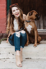 A young woman posing for pictures with her dog in the city
