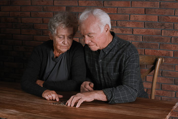 Poor elderly couple counting coins at table