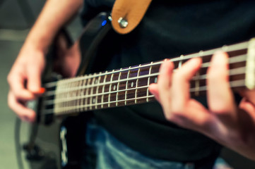 Hands the bass player. Closeup. Playing the guitar. Selective fo