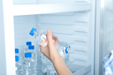 Woman taking bottle of water from refrigerator, closeup