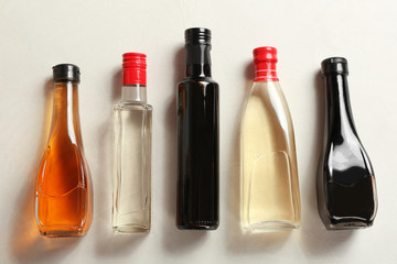 Bottles with different kinds of vinegar on light table, top view