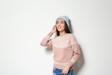 Young woman in warm sweater and knitted hat on white background. Celebrating Christmas