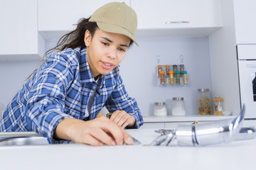 young female plumber working on sink