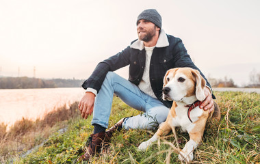 Man with beagle dog sitting together near the lake