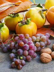 persimmons, grapes,  quince and walnuts on a rustic wooden table with leaves, vertical