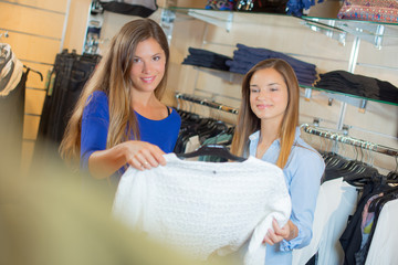 Two ladies looking at jumper in clothes shop
