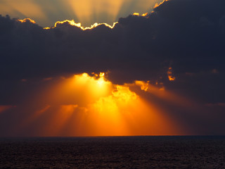 dramatic sunset over the sea with rays of light emerging from dark illuminated clouds over a calm ocean