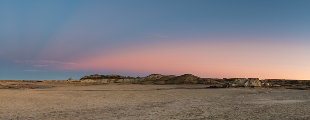 Panorama of the desert landscape and hills of the Bisti Badlands of New Mexico at sunset under a beautiful dramatic sky with blue, pink, peach, and purple hues