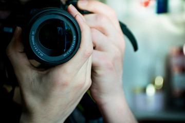 Closeup of dslr camera lens holding by a professional photographer looking front and  taking photo with blurred background