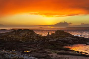 Angler on coastal rocks at sunset
