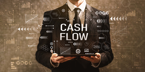 Cash flow with businessman holding a tablet computer on a dark vintage background