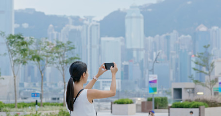 Woman take photo on cellphone in Hong Kong city
