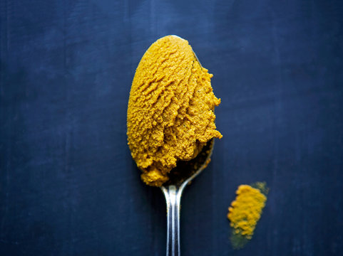 Turmeric paste in a spoon rests on a blue surface.
