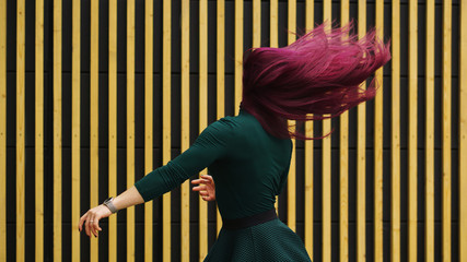 Cute young girl dancing on simple geometric background. Girl has eggplant hair flying in motion....