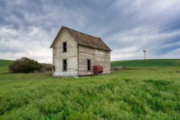 abandoned house in field with windmill