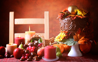 Thanksgiving Fall table setting with Autumn theme chocolate cake, cornucopia and candles.