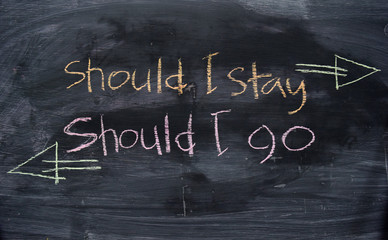 Should I stay or Should I go written with color chalk concept on the blackboard