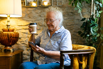 Sweet senior woman using her phone at a cafe