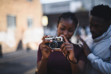 Man teaching his girlfriend how to use a vintage film camera