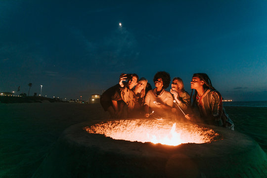 Friends roasting marshmallows over a bonfire