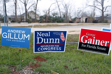Campaign signs stand near a new polling location where Hurricane Michael destroyed many schools and other buildings used as polling stations in the area in Lynn Haven