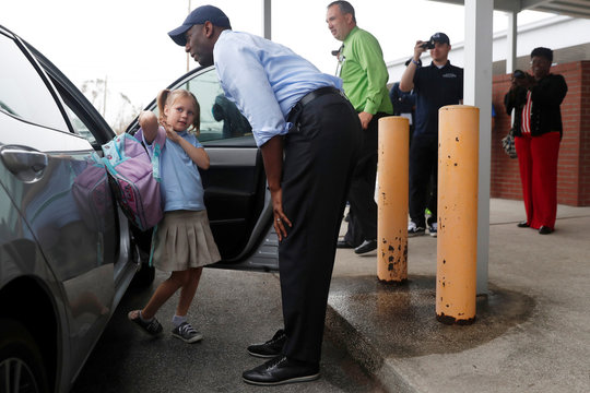 Democratic gubernatorial candidate Andrew Gillum greets Summer Flowers, 6, as she arrives for the first day of class since Hurricane Michael at Parker Elementary School in Parker
