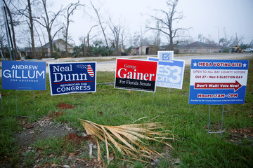 Campaign signs stand beside a sign directing voters to a new polling location where Hurricane Michael destroyed many schools and other buildings used as polling stations in the area in Lynn Haven
