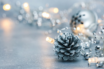 glowing christmas lights garland and pine cone with jingle bell on blurred silver background