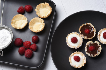 Flat lay of chocolate and vanilla custard fillo shells topped with raspberries
