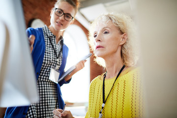 Mature manager looking at computer screen where her young colleague pointing while explaining data