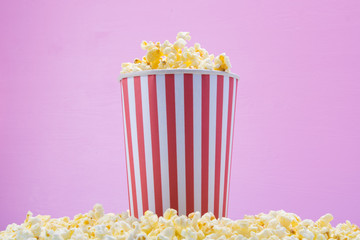 on a pink background is a glass in a sprinkled popcorn, filled to the top