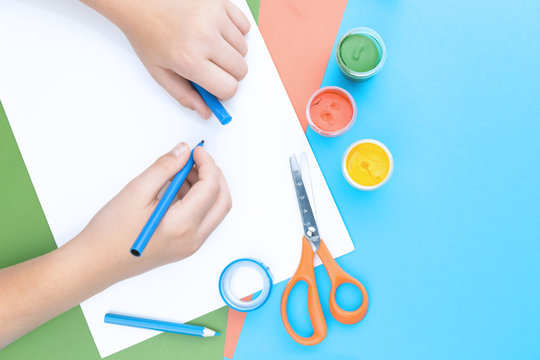 Color paper in blue, pink and green, paint, scissors and hands of a child drawing with blue pen top view flat lay, copy space