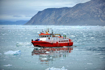 Red ship in the sea among the ice
