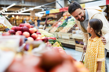 Cheerful careful father with beard touching shoulder of daughter and asking her about food preferences while they choosing organic food at farmers market