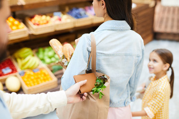 Close-up of man stealing wallet from bag of young lady walking with daughter in fresh food shop, thief taking purse out of shopping bag