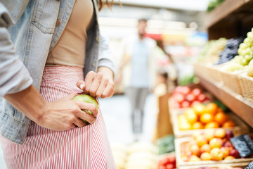Close-up of unrecognizable woman in stripped skirt hiding apple in pocket while stealing it in food...