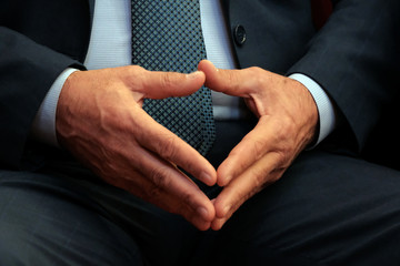Male hands closeup. Fingers touch each other in the form of a triangle. Abstract middle aged man in a suit. The concept of an official or a businessman in anticipation.