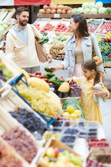 Positive beautiful young family choosing fresh fruits and vegetables while walking together in farmers market, they leading healthy lifestyle
