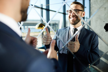 Successful businessman looking in mirror and showing thumbs up to himself