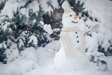 snowman in the forest in Christmas clothes, next to the tree