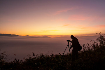 Photographer take photos with mirror camera on peak of mountain. misty landscape, spring orange pink misty sunrise in beautiful valley below.
