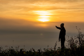 Silhouette of man standing on top mountain looks into the distance at morning misty landscape