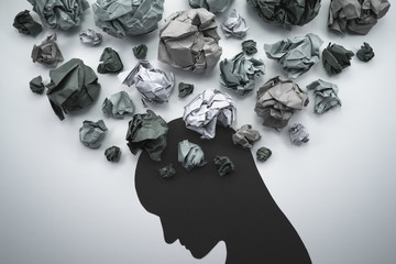 Silhouette of troubled person head. Concept image of anxiety and negative emotion. Waste paper and head silhouette.