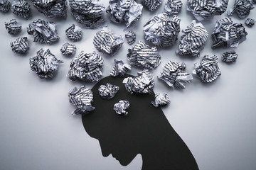 Silhouette of depressed and stressed person head. Concept image of negative emotion. Waste paper and head silhouette.