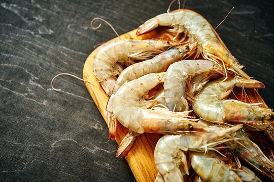 fresh delicious raw tiger prawns on a wooden board on a black wooden table