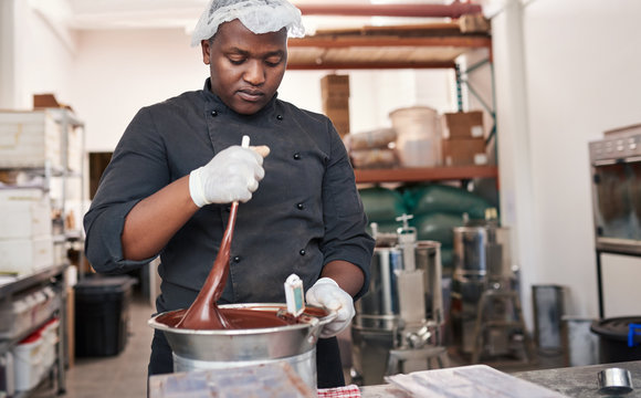 Worker using a bain marie to mix melting chocolate