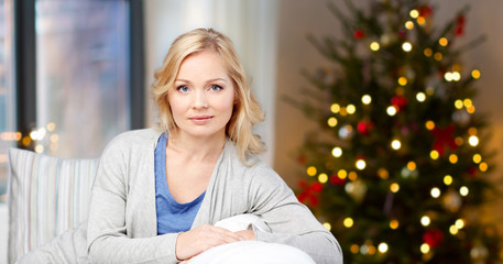 holidays and people concept - middle aged woman over christmas tree background at home