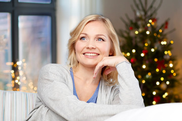 holidays and people concept - happy middle aged woman over christmas tree background at home