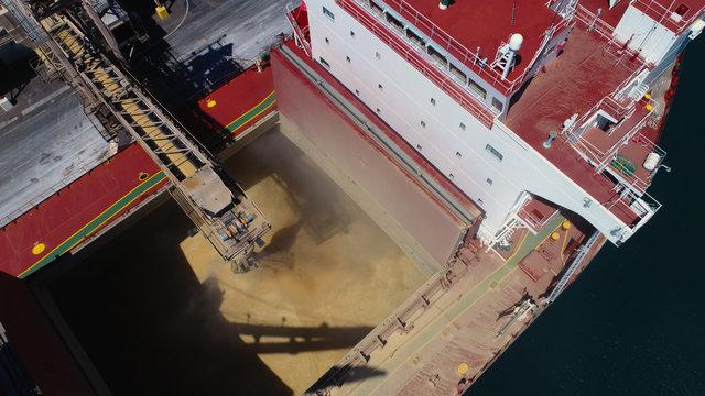 Tight drone shot of ship loading bulk grain in Australian port.